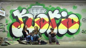 Kolme nuorta istuu Haapaniemn pysäköintitalon graffitin edessä.