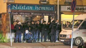 Mellakkapoliisi jututti miesjoukkiota Hägerstenin kaupunginosassa Tukholmassa varhain toukokuun 25. päivän aamuna.
