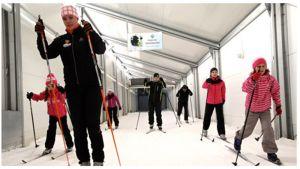 Lapsia ja aikuisia hiihtämässä hiihtoputkessa.