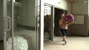 Nainen kantaa suurta palloa liiketilassa.