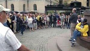 Mielenosoittajia Kolmen sepän patsaalla Helsingissä.