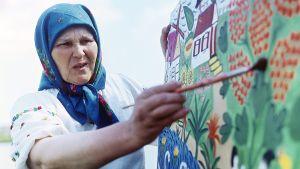 Ukrainalainen taiteilija Maria Primatšenko maalamassa Bolotnjan kylässä vuonna 1967.
