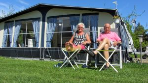 Anne-Maj ja Rolf Andersson istuvat ulkona asuntovaunun vieressä.