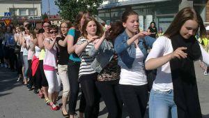 Ihmiset tanssivat letkajenkkaa torilla.