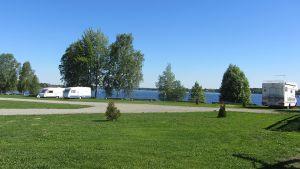 Asuntovaunuja ja matkailuauto joen rannassa.