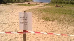 Maa-ampiaisista varoittava kyltti Niuvan uimarannalla Kuopiossa