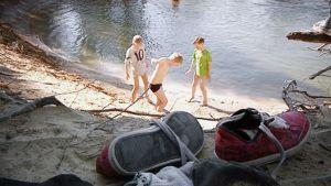 Pikkupojat leikkivät rantavedessä.