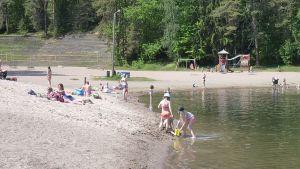 Helteisen kesäpäivän viettäjiä uimarannalla.