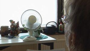 Vanhuksen huoneeseen on tuotu tuuletin kuumana kesäpäivänä.