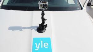 Videokamera on asennettu Ylen auton konepeltiin.
