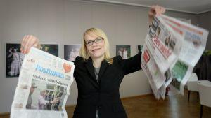 Tutkimuksesta vastannut lehtori Päivi Tirkkonen pitää käsissään virolaisia Postimees ja Eesti Päevaleht -sanomalehtiä Suomi-Viro -media-analyysin tulosten esittelytilaisuudessa Helsingissä 5. kesäkuuta 2013.