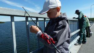 Poika kalastaa.