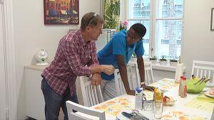 Perheryhmäkodin johtaja Pekka Ihalainen ja Yannick Tshimanga pöydän äärellä