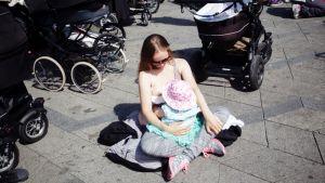 Mielenosoitukseen osallistuva nainen imettää lastaan kadulla Kööpenhaminassa.