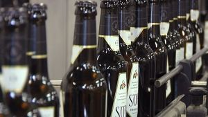 Kaskeinmarjan Sör-omenasiideri pulloja kulkee panimon lijastolla.