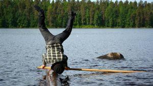 Hannu Kettunen seisoo käsillään tukin päällä.