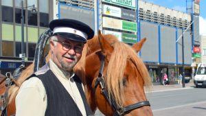 Vossikka-ajuri Matti Niiranen pitelee hevosta.