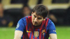 Lionel Messi istuu nurmella.