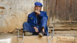 He Feng Xing istuu tupakalla kyläsairaalan piha-alueella.