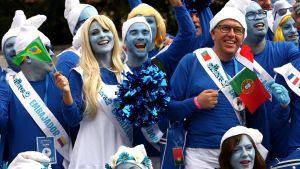 Ihmisillä on hauskaa smurffipäivänä. He heiluttavat eri maiden lippuja väkijoukossa.