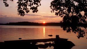 Auringonlasku järven rannalla.