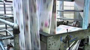 Sanomalehtipaperi vilistää painokoneen läpi.