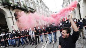 Naamioituneet nuoret osoittavat mieltään Italian Torinossa vappupäivänä.