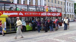 Matkailijoita kiertoajelubussin edustalla Helsingin Senaatintorilla kesäkuussa 2013.