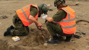 Kaksi miestä kaivaa maasta ammusta.