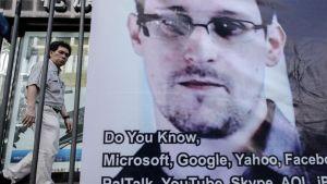 Ohikulkija käveli Edward Snowdenia tukevan bannerin ohi Hongkongissa 18. kesäkuuta.