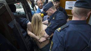 Poliisi poistaa tukholmalaisessa moskeijassa mieltään osoittaneita Femen-aktivisteja paikalta.