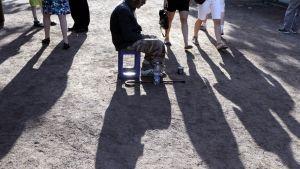 Mies kerjää Esplanadin puistossa