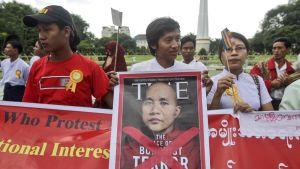 """Time-lehden kansi otsikolla """"Buddhalaisterrorin kasvot"""" mielenosoittajien käsissä."""