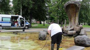 Mies puhdistaa Tyrsky-patsaan allasta