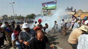 Syrjäytetyn presidentin Muhammad Mursin kannattajat pakenevat eri suuntiin, kun väkijoukon keskelle on ammuttu savupanos ja mahdollisesti kyynelkaasua.