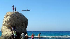 Nuori poika hyppää Välimereen kalliolohkareelta.