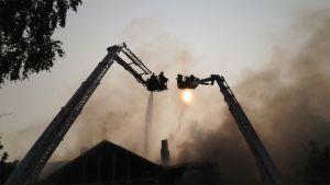 Palomiehet sammuttavat tulipaloa ylhäältä päin nostureiden koreista