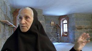Lintulan luostarin nunna Maria esittelee kirkon vanhaa kivijalkaa.