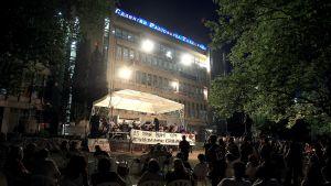 Ihmiset kuuntelevat Kreikan yleisradion ERT:n orkesterin esiintymistä yhtiön toimitalon edustalla.