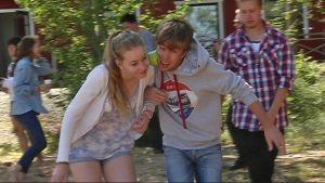 Tyttö ja poika kulkevat käsikynkässä ja kuljettavat omenaa poskiensa välissä.