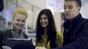 Kolme nuorta aikuista katsovat taulutietokonetta.
