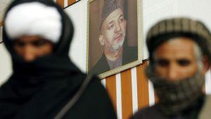 Afganistanin presidentti Hamid Karzain muotokuva näkyy entisten taliban-sotilaiden takana.