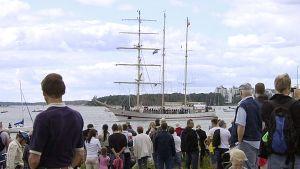 Ihmisiä on kerääntynyt runsaasti Suomenlinnan rantaan katsomaan Helsingistä lähtevien Tall Ships Race -alusten ohipurjehdusta.