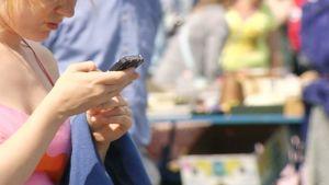 Nuori nainen käyttää kännykkää.