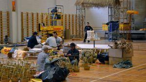 Kuvassa ihmiset rakentavat Turun normaalikoulun liikuntatiloissa koristeita buddhalaisleiriä varten.