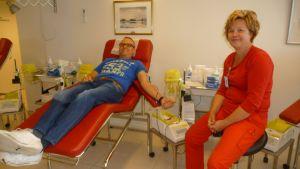 Mies makaa hoitotuolissa luovuttamassa verta ja sairaanhoitaja istuu vieressä.