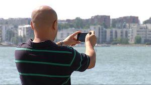 Blogi-kirjoittaja ottaa kuvaa Lauttasaaren rannassa.