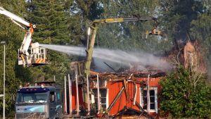 Palokunta ruiskuttaa vettä palaneeseen taloon