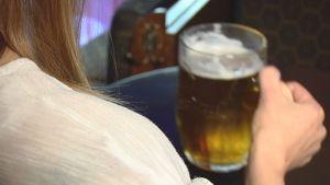 Nainen juomassa olutta.