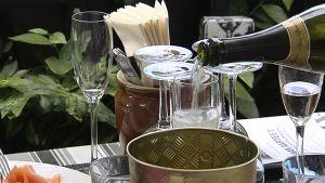 Kuohuviiniä kaadetaan lasiin ravintolan pöydässä.
